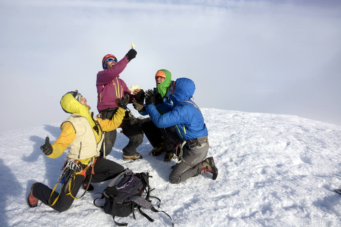 The team kneels on the summit in awe before a piece of Swiss cheese. One of the expedition's sponsors was a Swiss cheese company that provided 25 kilograms of its finest product. Left to right are Antoine Moineville, Fabio Lupo, Christian Ledergerber and Jerome Sullivan. [Photo] Silvan Schuepbach