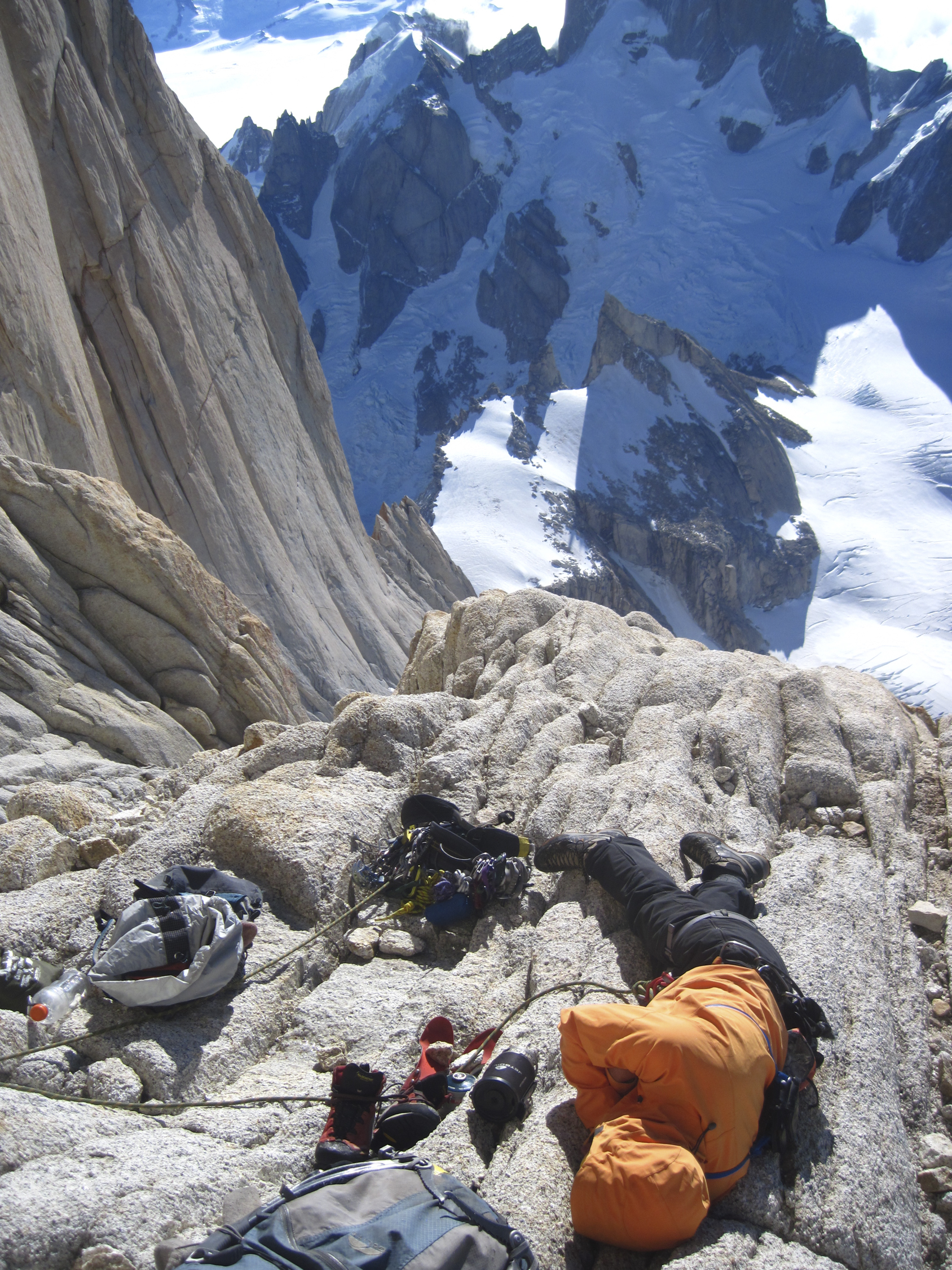 Josh Huckaby catches a little catnap on the three-star ledge high on the North Pillar on Fitz Roy in 2012. He writes, We arrived here too early to actually bivy, because it was still sunny and warm. Plus neither Troutman nor I had a sleeping bag to curl up in together. [Photo] Josh Huckaby Collection