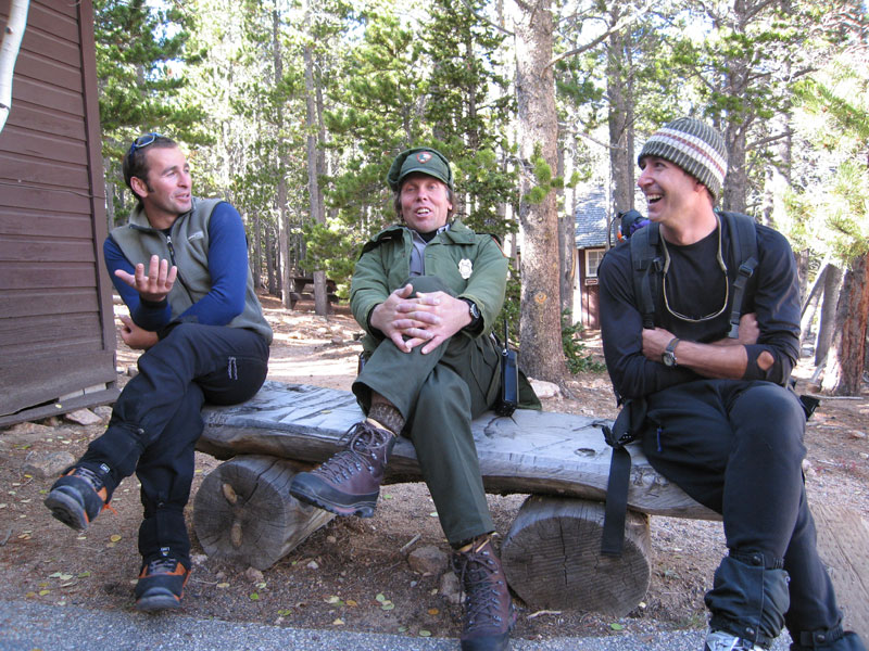 Alex Kostadinov, Jim Detterline and Mark Ronca tell tales at the Longs Peak Ranger Station, September 2005.  The photographer recalls, Jim was stationed at the cabin that day, and Alex, Mark and I stopped by to chat with our friend after a failed attempt on the Smear of Fear (III WI6 M5) on the East Face of Longs Peak. [Photo] Lisa Foster