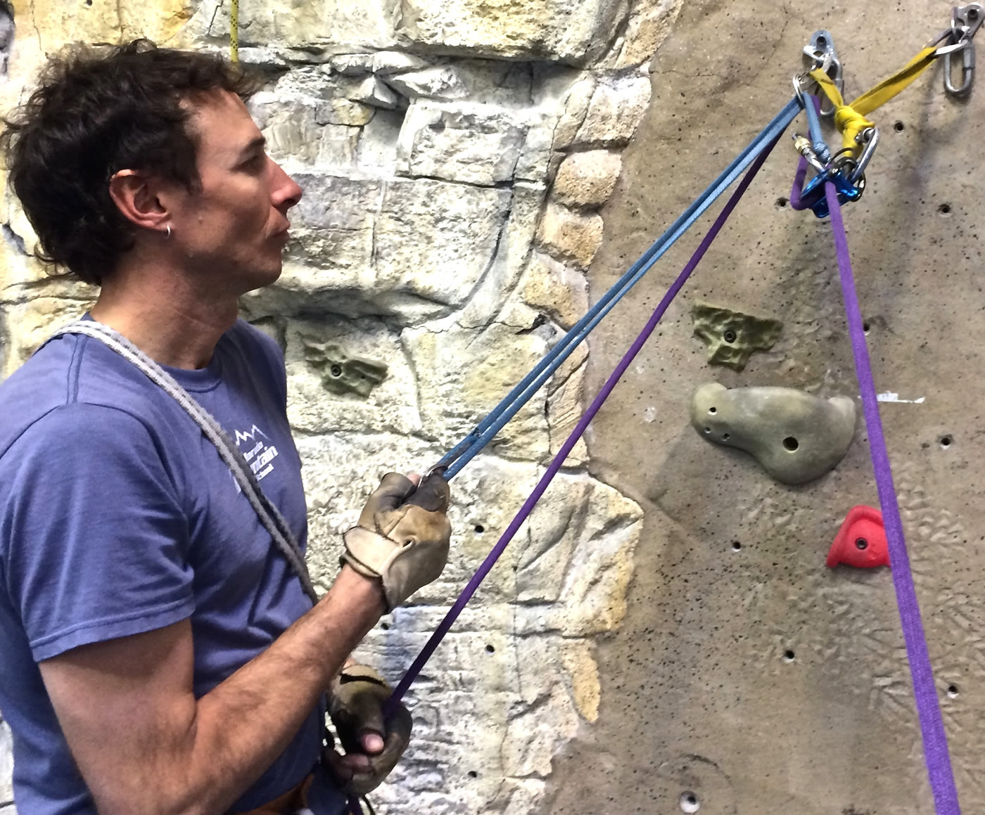 Mike Lewis demonstrates how to lower a climber while in guide mode with the DMM Pivot: The belayer can set up a sling to pull back the carabiner on the rope and release the friction on the brake-end of the rope, allowing it to slide through the device while maintaining control with the brake hand. It may be necessary to use a backup on the brake-side of the rope to ensure control.