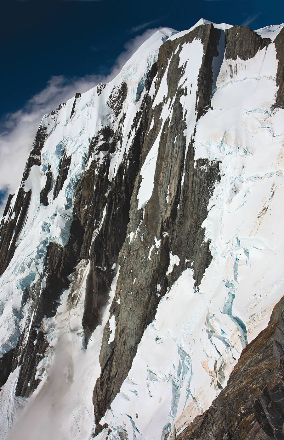 The Central Spur and Right Flank of the West (Spencer) Face of Elie de Beaumont, viewed from the West Rib of Mt. Walter. The left-hand dome is the summit. Rob Rainsbury and John Visser established the classic Central Spur in 1972. Kester Brown, editor of The Climber, the New Zealand Alpine Club magazine, says: Despite the elegance of the line... I'd be surprised if this route has had a single ascent in the last twenty years. Glacial recession vastly increased the difficulty of the multiday approach. [Photo] Kester Brown