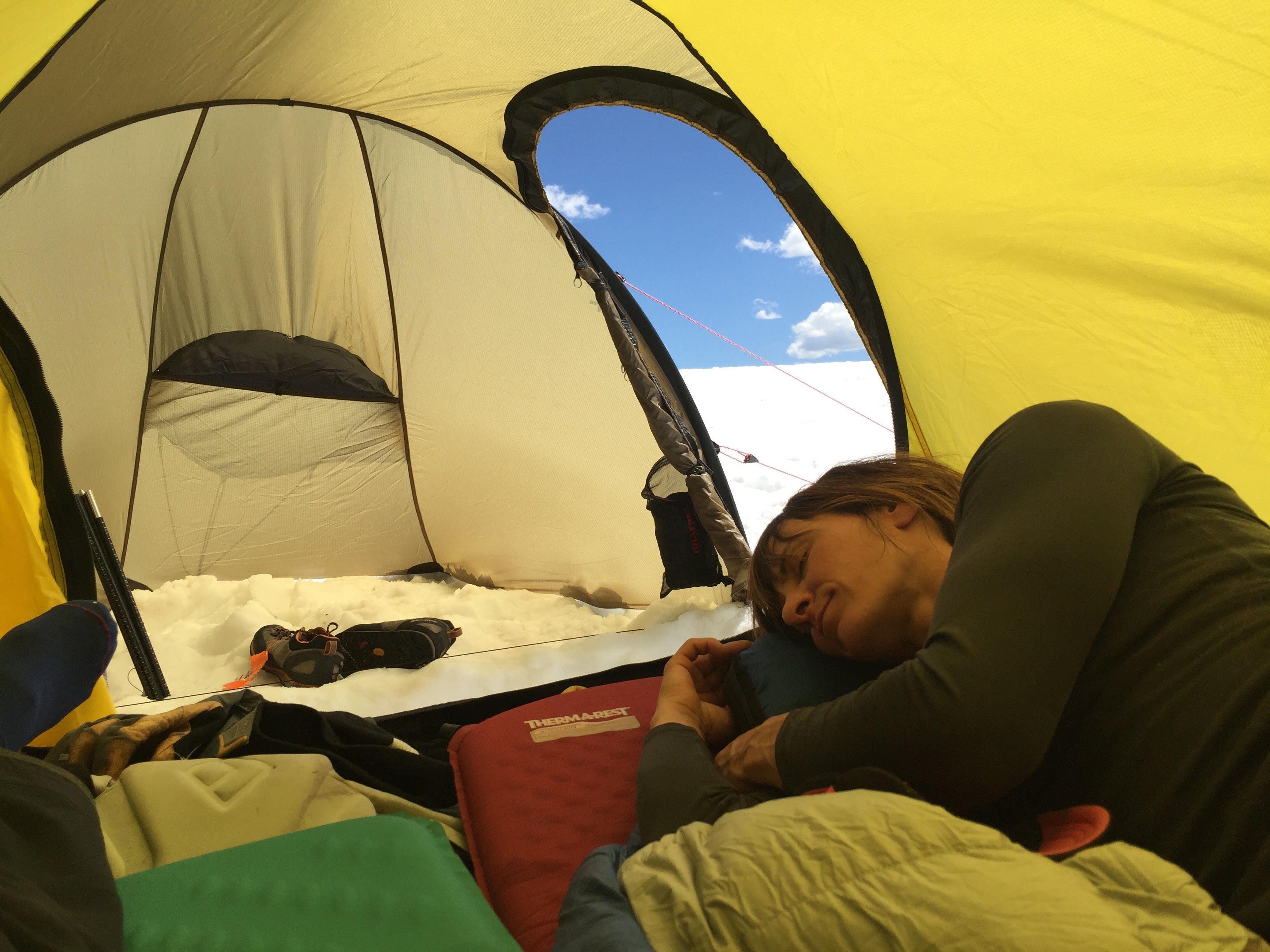 Mary Harlan dozes in the Hilleberg Nammatj 2 GT with the door open to the roomy vestibule. [Photo] Lance Torre