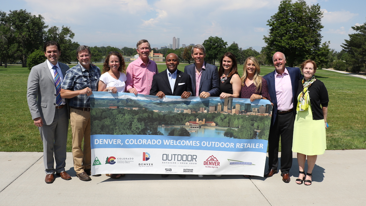 A deal was confirmed today that the summer Outdoor Retailer trade show will move to Denver, Colorado, next year. Pictured from left to right are Luis Benitez, director of Colorado's Outdoor Recreation Industry Office; Darrell Denny, executive vice president of Emerald Expositions; Amy Roberts, executive director, Outdoor Industry Association; Governor John Hickenlooper; Mayor Michael Hancock; Nick Sargent, president of SnowSports Industries America; Rachel Benedick, VP sales and service, Visit Denver; Marisa Nicholson, Outdoor Retailer show director; Richard Scharf, president and CEO, Visit Denver; Lieutenant Governor Donna Lynne. [Photo] Courtesy of Ground Floor Media