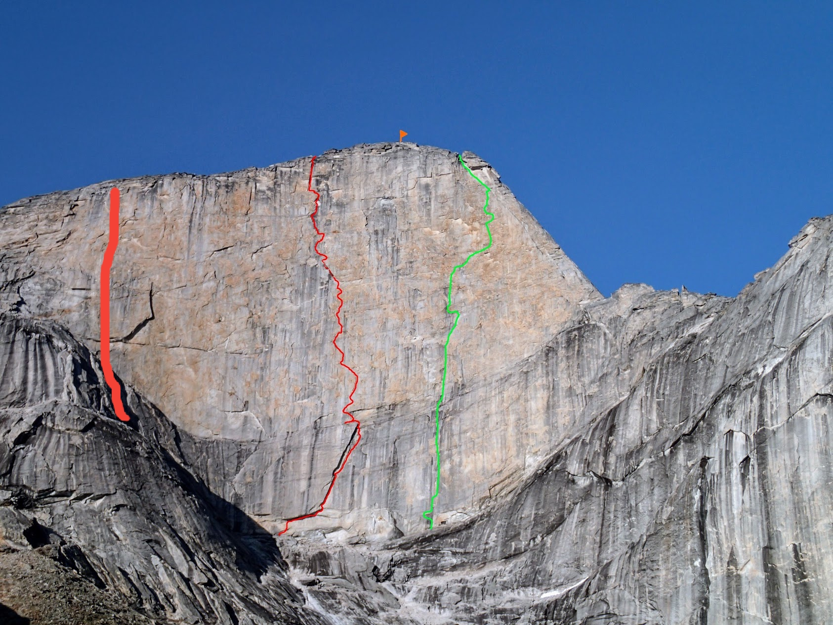 The west face of Xanadu: Golden Petals (V 5.13+ or 5.12 A0, 14 pitches) is marked in green on the right, Une pas mes (VI 5.10b A4/A4+, 11 pitches) is marked by the thin red line at center; the third route, Arctic Knight (V 5.11+, 7 pitches, ca. 1,600'), is marked in a thicker red line to the left of the previous two. [Photo] Engberg, Bain, Boning and Braasch collection