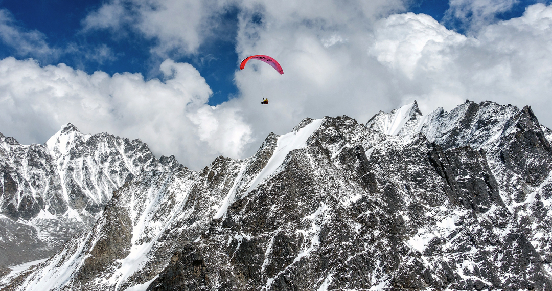 A view during the French climbers' trek to the Langtang Valley. The paraglider is a little east of the village of Sherpangau. The French bypassed three days of trekking with two hours of flying, albeit not without difficulty: On their first launch attempt they landed 400 meters lower than they had started. The conspicuous pointed rock and snow peak on the left is Peak 5857m. The rocky foreground ridge culminates in unnamed Peak 5613m. [Photo] Dusserre/Girard Collection