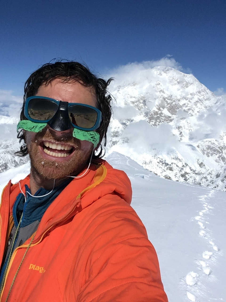 Self-portrait on the summit of Begguya (14,573'). Denali (20,310') is in the background. [Photo] Colin Haley