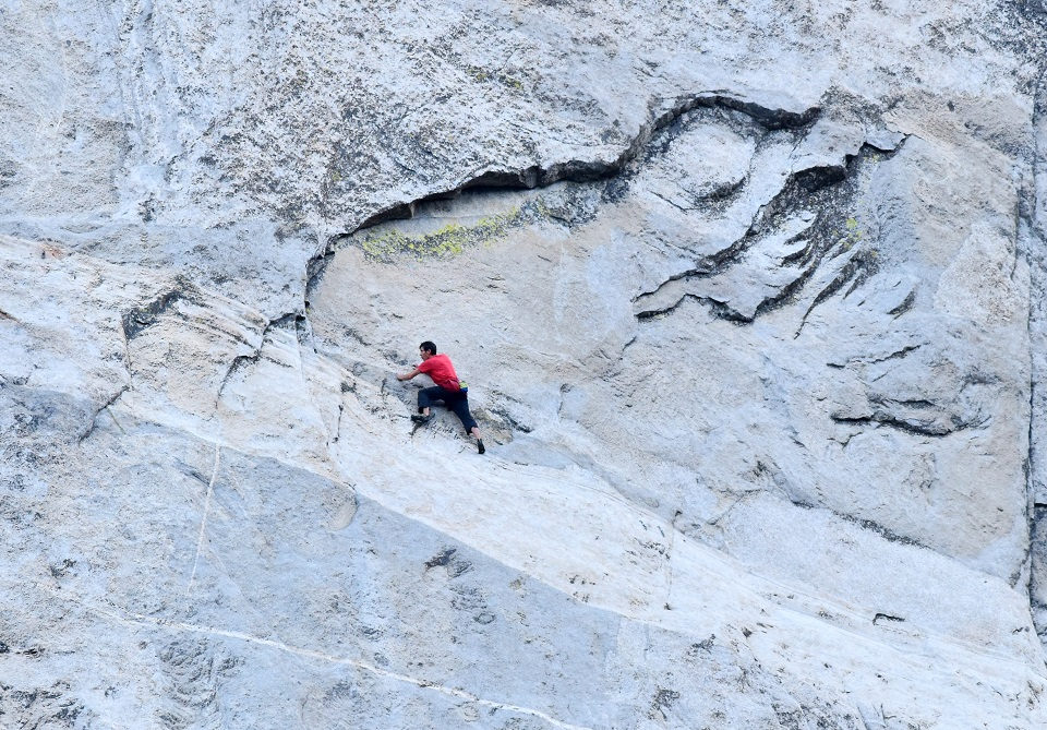 In this photo that was taken through a telescope from the ground, Alex Honnold carefully makes his way across the highly technical, friction-dependent moves low on the Freerider route (VI 5.13a, 3,000') during his historic ropeless ascent of El Capitan, June 3. [Photo] Tom Evans