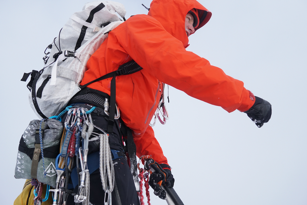 The Alpha-SV works well for alpine climbing; the long hem stays tucked under a harness, chest pockets are easy to access, and the long sleeves, ample hood, and high chin provide excellent coverage from the elements. In this photo Drew Thayer (the author) is wearing the jacket on the first ascent of Spearhead Peak (7,140'), Neacola Range, Alaska. [Photo Craig Muderlak]