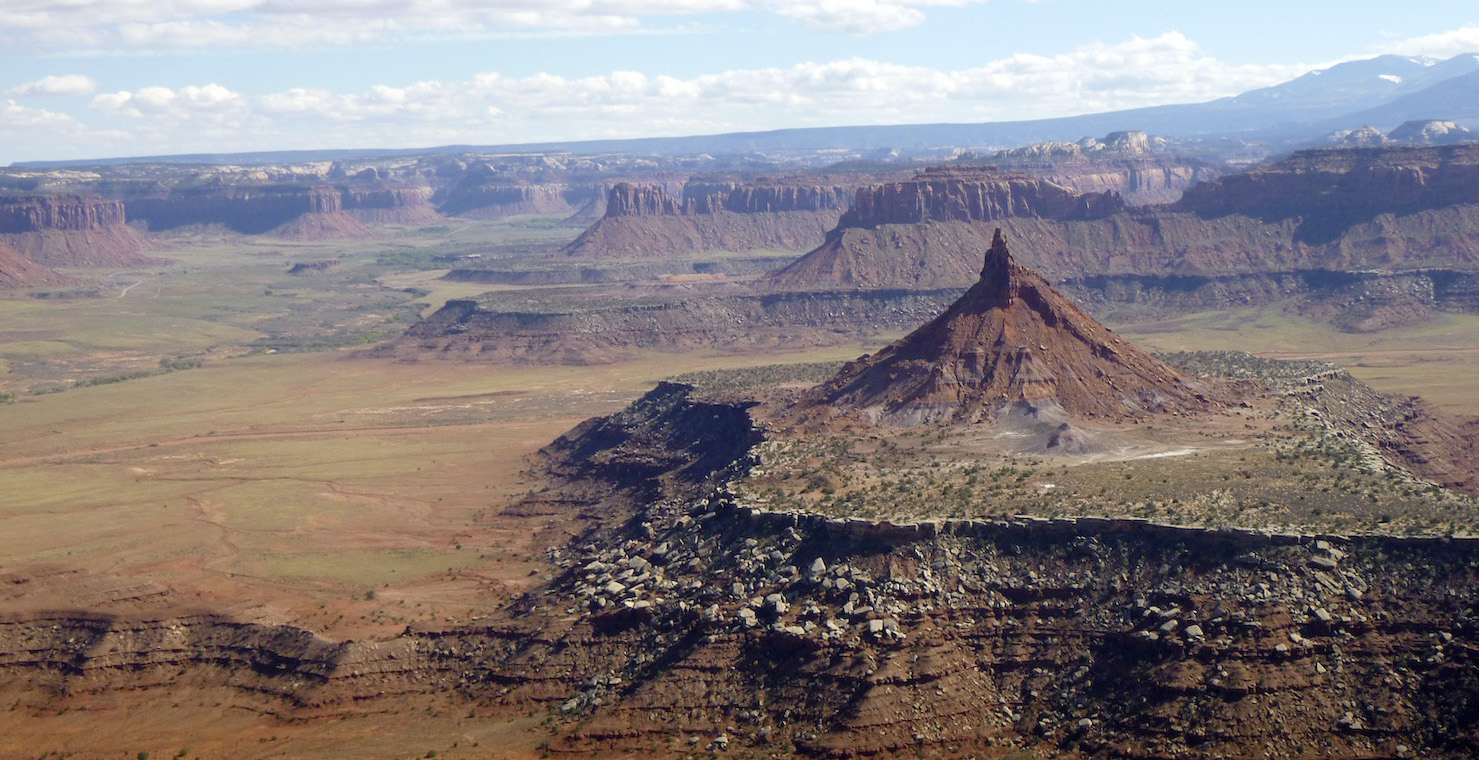 Looking east from the summit of North Six Shooter provides a glimpse of the 1.35-million-acre Bears Ears National Monument. South Six Shooter is in the foreground and Bridger Jack Butte and pinnacles are in the middle ground. The Abajo Mountains are in the background to the right and the La Sal Mountains are just out of view to the left. [Photo] Derek Franz