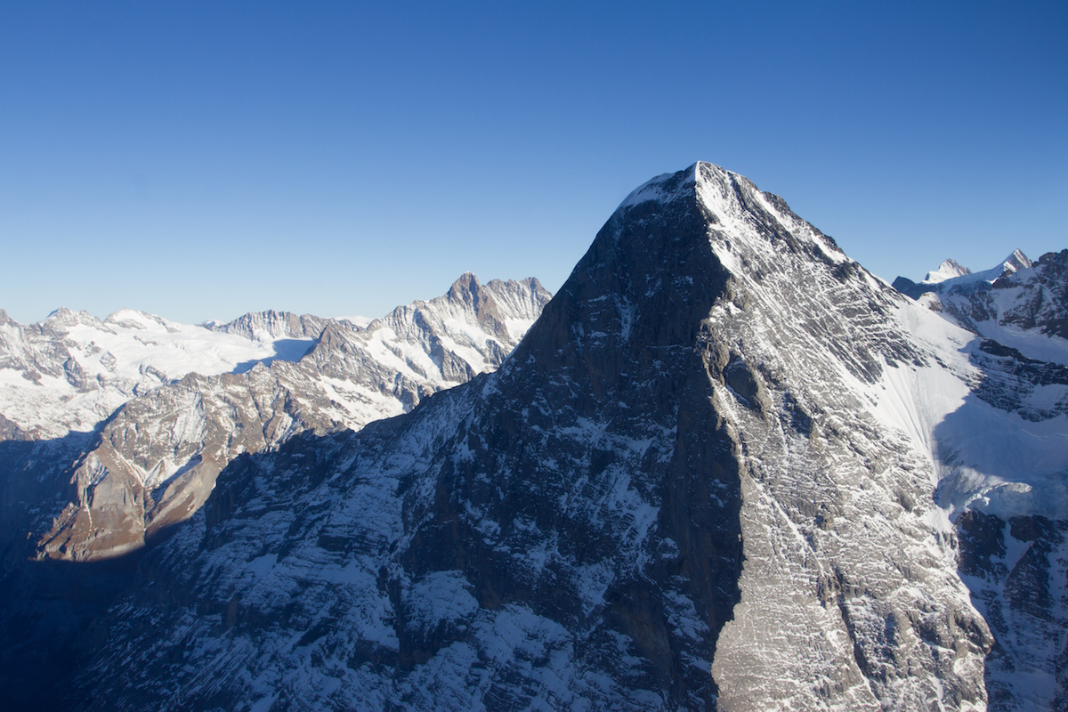 This aerial shot shows the magnitude of the Eiger North Face (3970m). Metanoia (VII 5.10 M6 A4, 1800m) takes a central line up the shadowy face. [Photo] Archive Metanoia