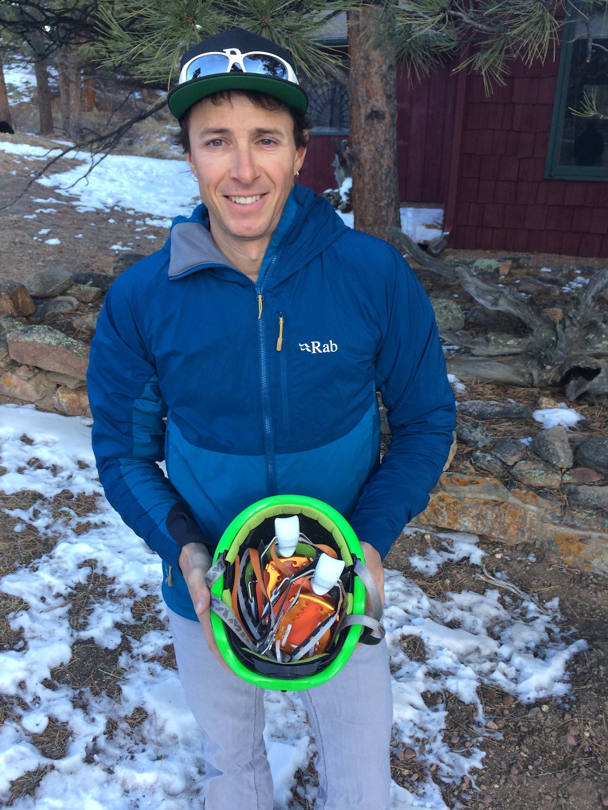 Mike Lewis shows how the Irvis Hybrid Crampons easily fit in a helmet. [Photo] Chris Wood
