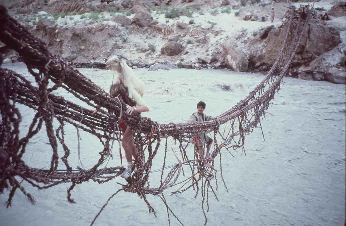 John Roskelley carrying a live goat on his back across the Dumordu River during the approach to Great Trango Tower, Pakistan, 1977. [Photo] Galen Rowell, Kim Schmitz collection