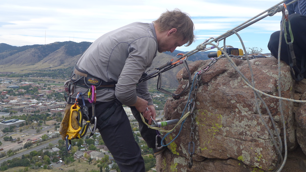 A volunteer with the Boulder Climbing Community replaces bolts on North Table Mountain above Golden, Colorado. [Photo] Jason Haas