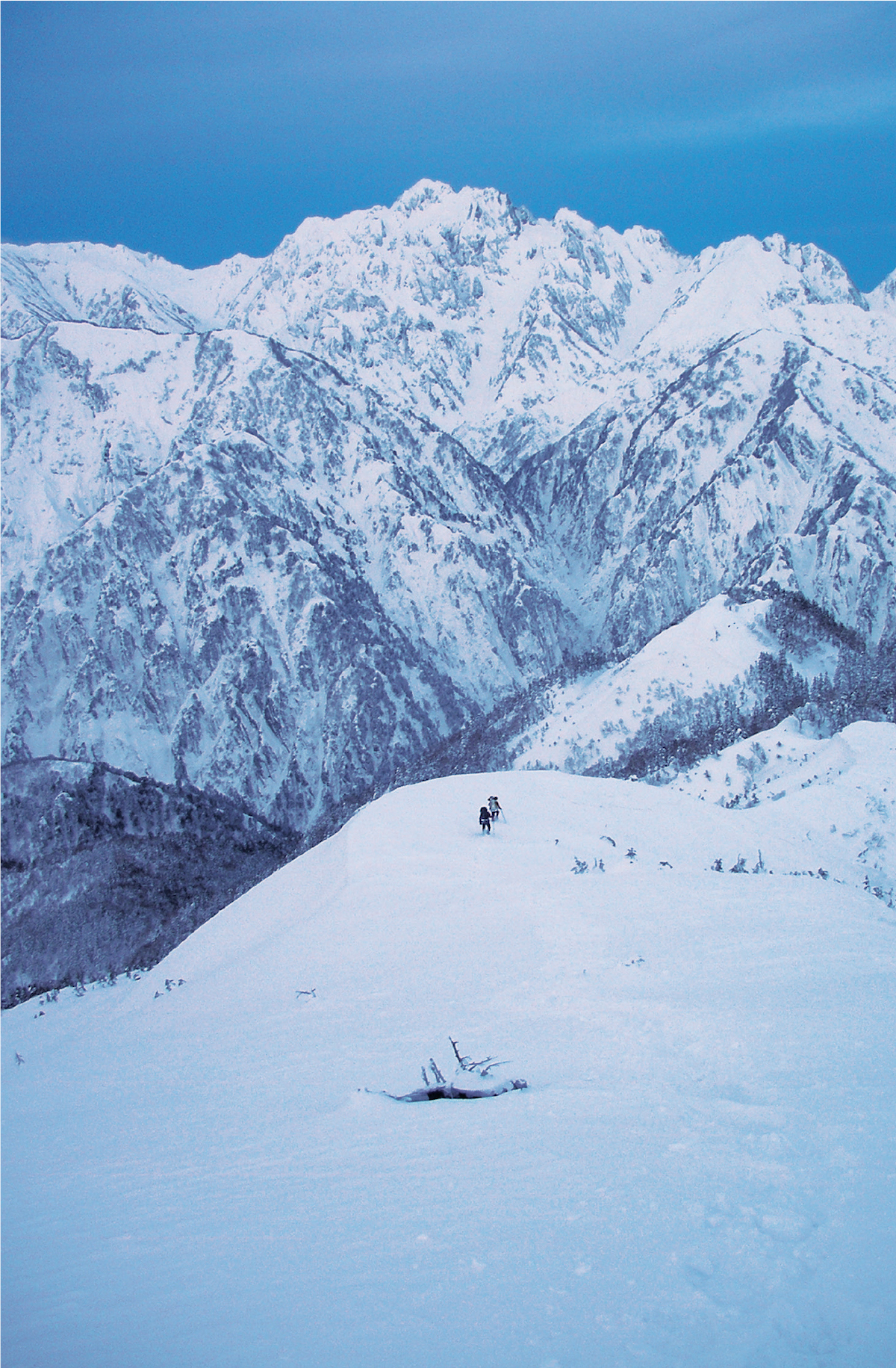 The author and Fumitaka Ichimura play Pachinko on the Kurobe Traverse, Japanese Alps. The apex of the traverse, Mt. Tsurugi (2999m), symbol of Japanese mountaineering, is visible as the highpoint in the distance. From where they are in this photo, the climbers have to descend to the Kurobe River, cross the next mountain and then keep climbing to Mt. Tsurugi. They managed the traverse in the heart of winter in fourteen days. [Photo] Yusuke Sato