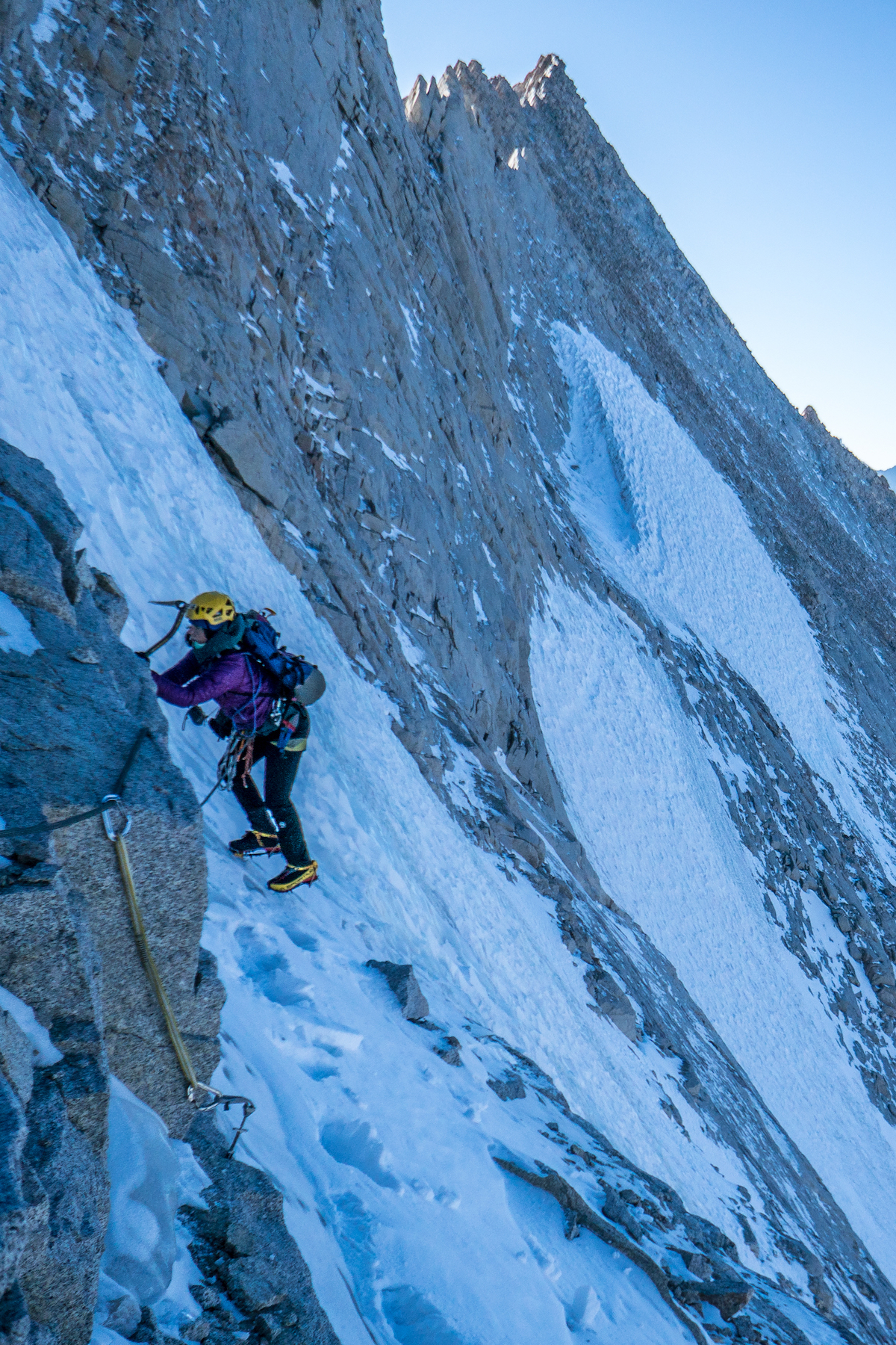 Whitney Clark traverses to the belay after climbing the hanging glacial ice midway up a new route (Land of Milk and Honey, IV 5.8+ M3 R 65 degrees, 1,000') on the northwest face of Mt Russell (14,094') in the Sierra Nevada Range, California. [Photo] Tad McCrea