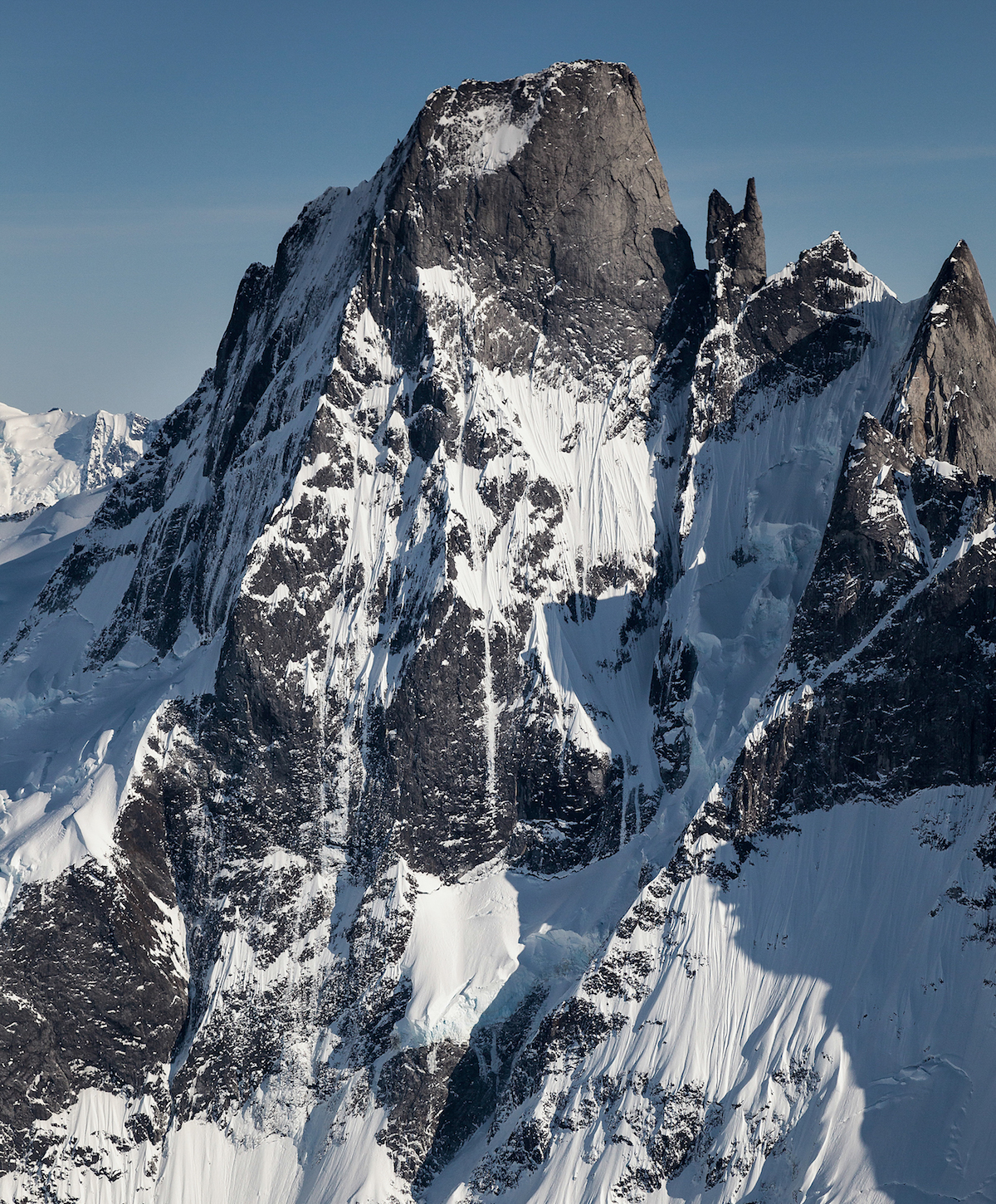 Devils Thumb, North Pillar (left) and northwest face (center). The face has never been climbed in its entirety. As Dieter Klose wrote in the 2003 American Alpine Journal, The wild face, discovered well over two decades ago, ends on a very specific summit. Here are all the makings of both post-modern and futuristic alpinism, yet it simply has not, does not, and seems not to be do-able. [Photo] John Scurlock