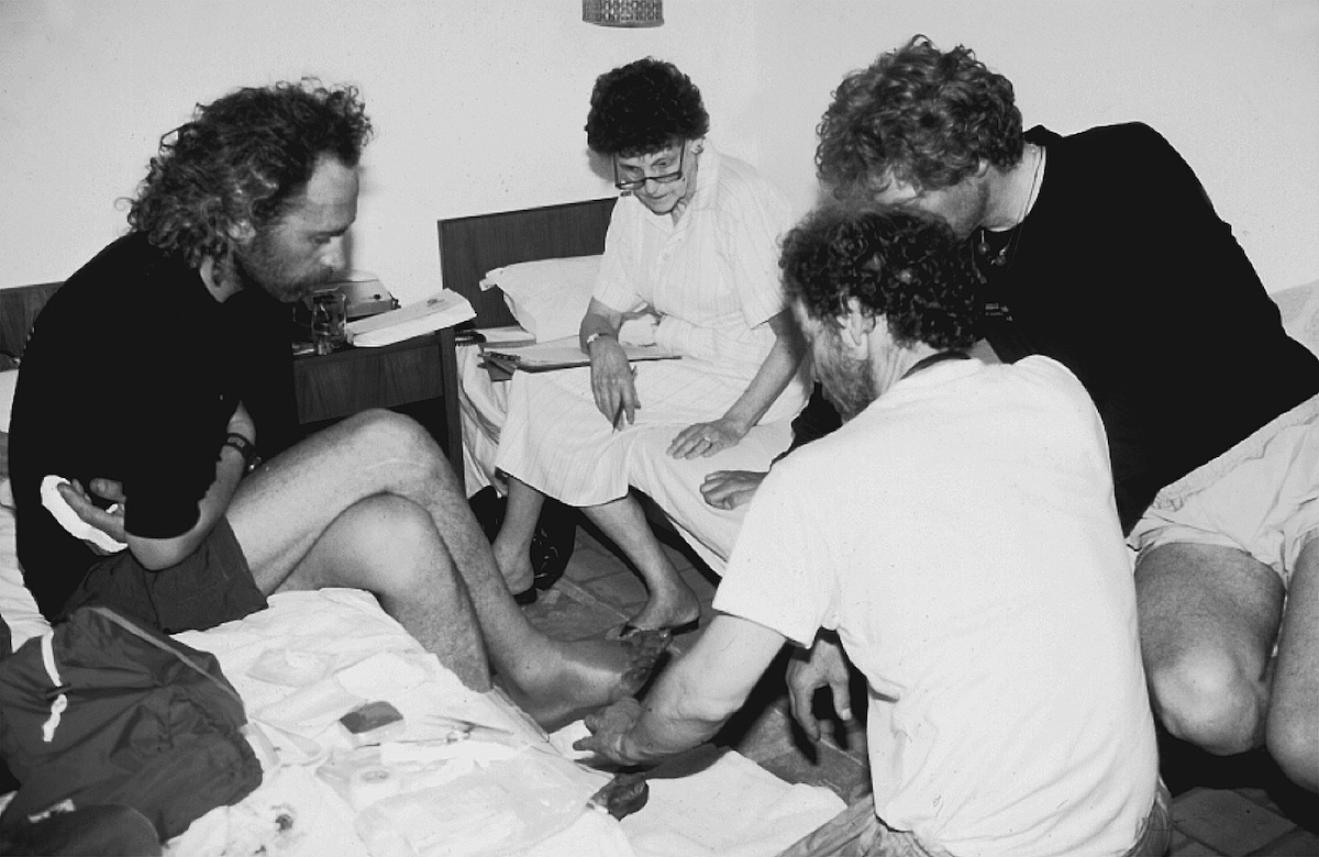 Hawley interviewing a climber with frostbitten toes. [Photo] Courtesy of the Michael and Meg Leonard collection