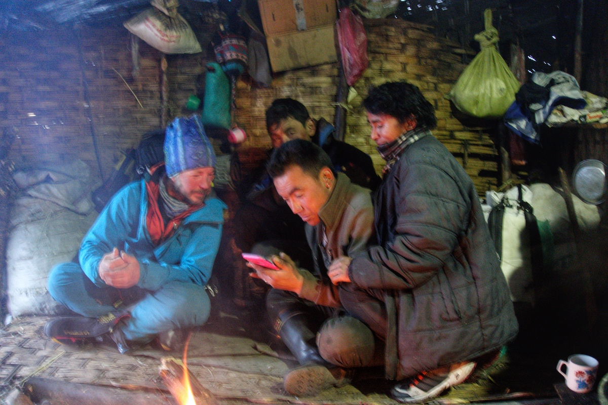 Kelley shows some pictures on his phone to some yak herders on the way down to Kathmandu. [Photo] Benjamin Billet