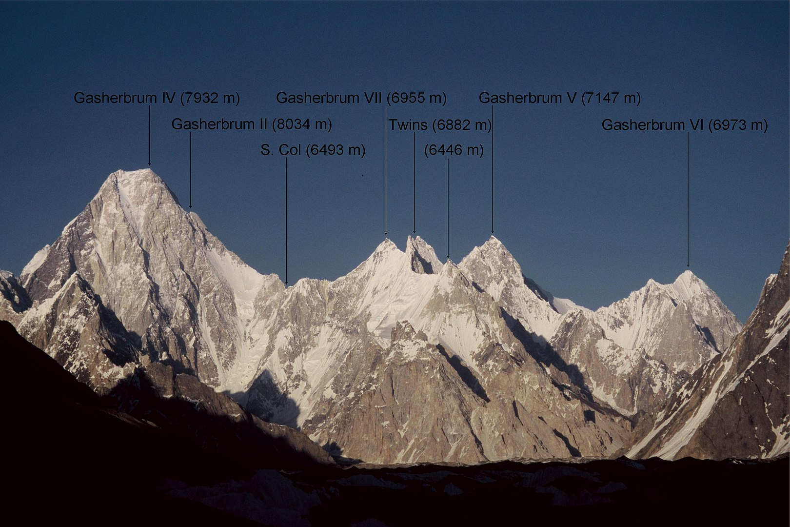 The west faces of Gasherbrum IV, V, VI, and VII. The peak of Gasherbrum II is just barely visible behind the southern ridge of Gasherbrum IV. Gasherbrum I (Hidden Peak) is hidden behind Gasherbrum V. [Photo] Florian Ederer, Wikimedia