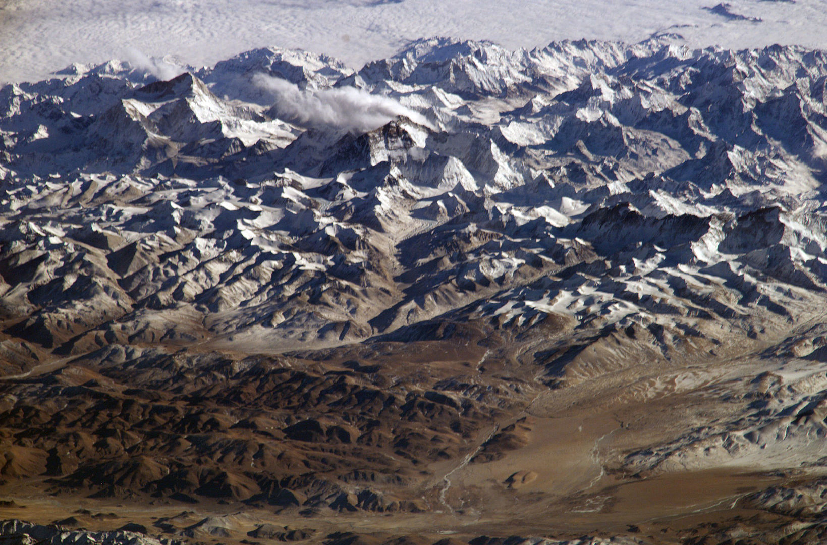 This photograph of the Himalaya was taken from the International Space Station in 2004. Visible from left to right are: Makalu, Chomolungma (Everest), Lhotse and Cho Oyu. [Photo] Courtesy of NASA, Wikimedia