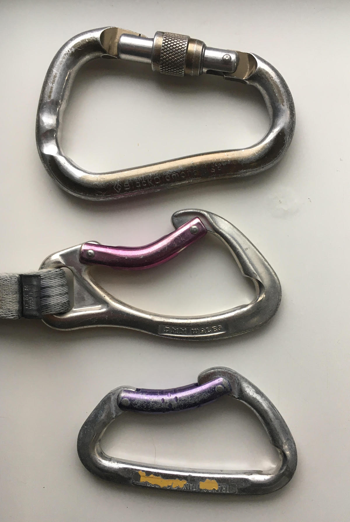 These carabiners were gouged by ropes. The top locking 'biner was used for a tube-style belay/rappel device, resulting in the double grooves. [Photo] Derek Franz