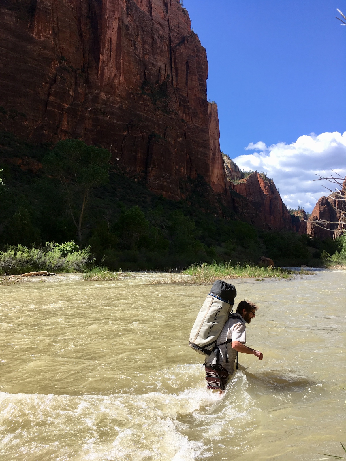 Kalman crossing a swollen Virgin River after climbing Moonlight Buttress. The Octapod fit neatly inside the medium-size haul bag seen here, along with sleeping gear, personal climbing gear, a rack, helmet and poo bag. [Photo] Nelson Klein