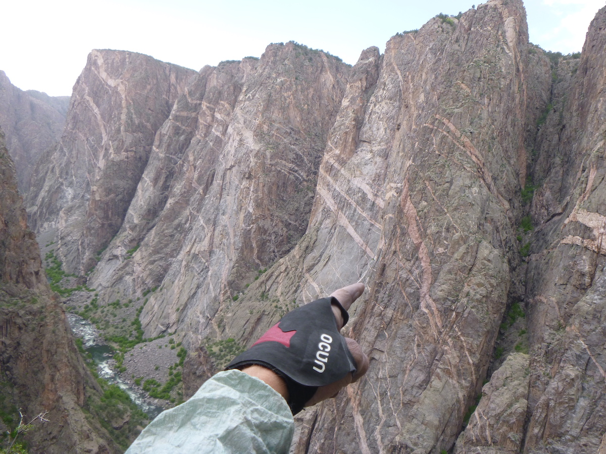 Sporting the Ocun Crack Gloves in the Black Canyon while pointing at climbers on the Russian Arete. [Photo] Derek Franz