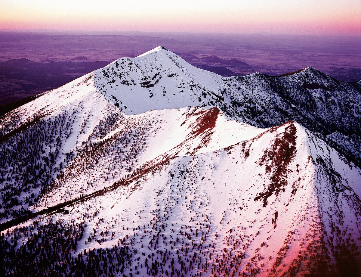 Pictured here at sunset, Dook'o'oosliid, or Humphreys Peak (12,633'), is the highest point in Arizona. Dook'o'oosliid was once part of a much larger stratovolcano that erupted hundreds of thousands of years ago. [Photo] Chuck Lawsen