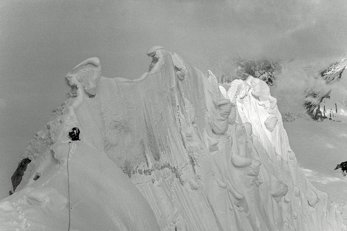 George Lowe, during the 1977 first ascent of the Lowe-Kennedy Route on the north face of Mt. Hunter (Begguya, 14,573'), Alaska Range. On an earlier attempt, Jeff Lowe fell near the sun-shadow line. [Photo] Michael Kennedy