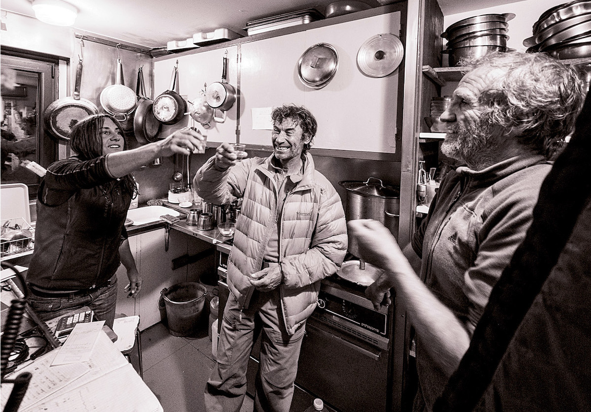 Inside the kitchen of the Promontoire Refuge, built in 1901 by the Club Alpin Francais (and rebuilt in 1966) at 3092 meters, guardians Nathalie Clerc and Fredi Meignan enjoy a glass of genepi with La Grave guide Pierre Cinquin. The summer of 2018 was Meignan's last after a decade as a guardian. He recalls the season as unusually warm. [Photo] Abdou Martin