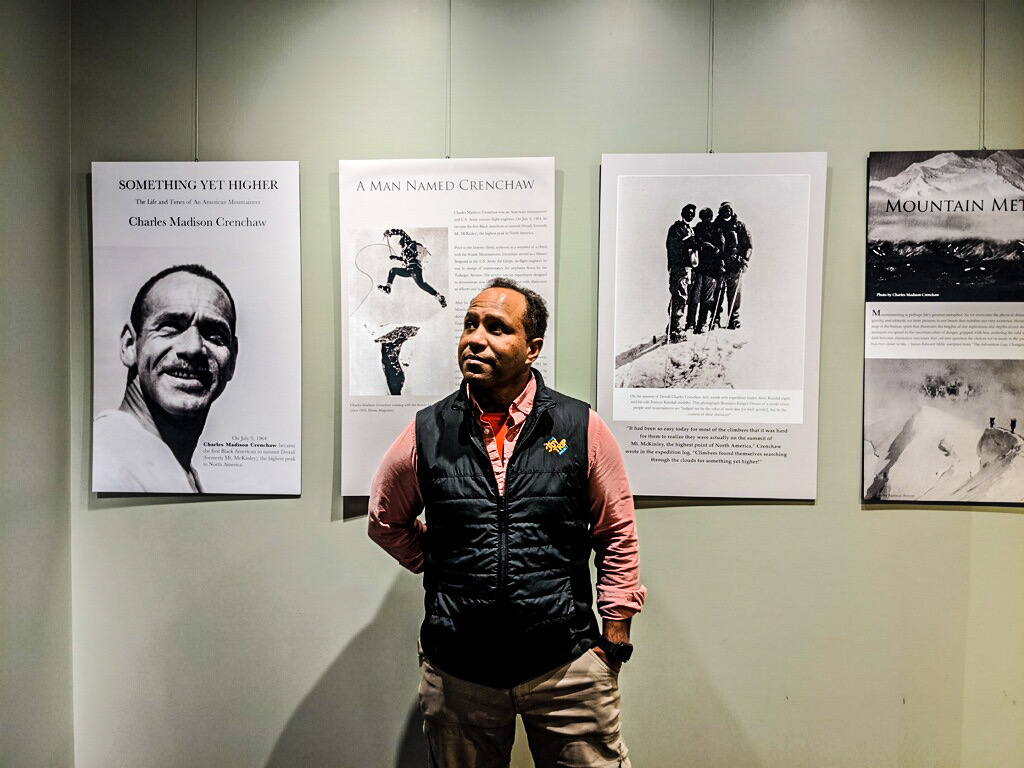 James Edward Mills stands in front of his exhibit featuring African American mountaineer Charles Madison Crenchaw at the Bradford Washburn American Mountaineering Museum, in Golden, Colorado. [Photo] Courtesy of James Edward Mills