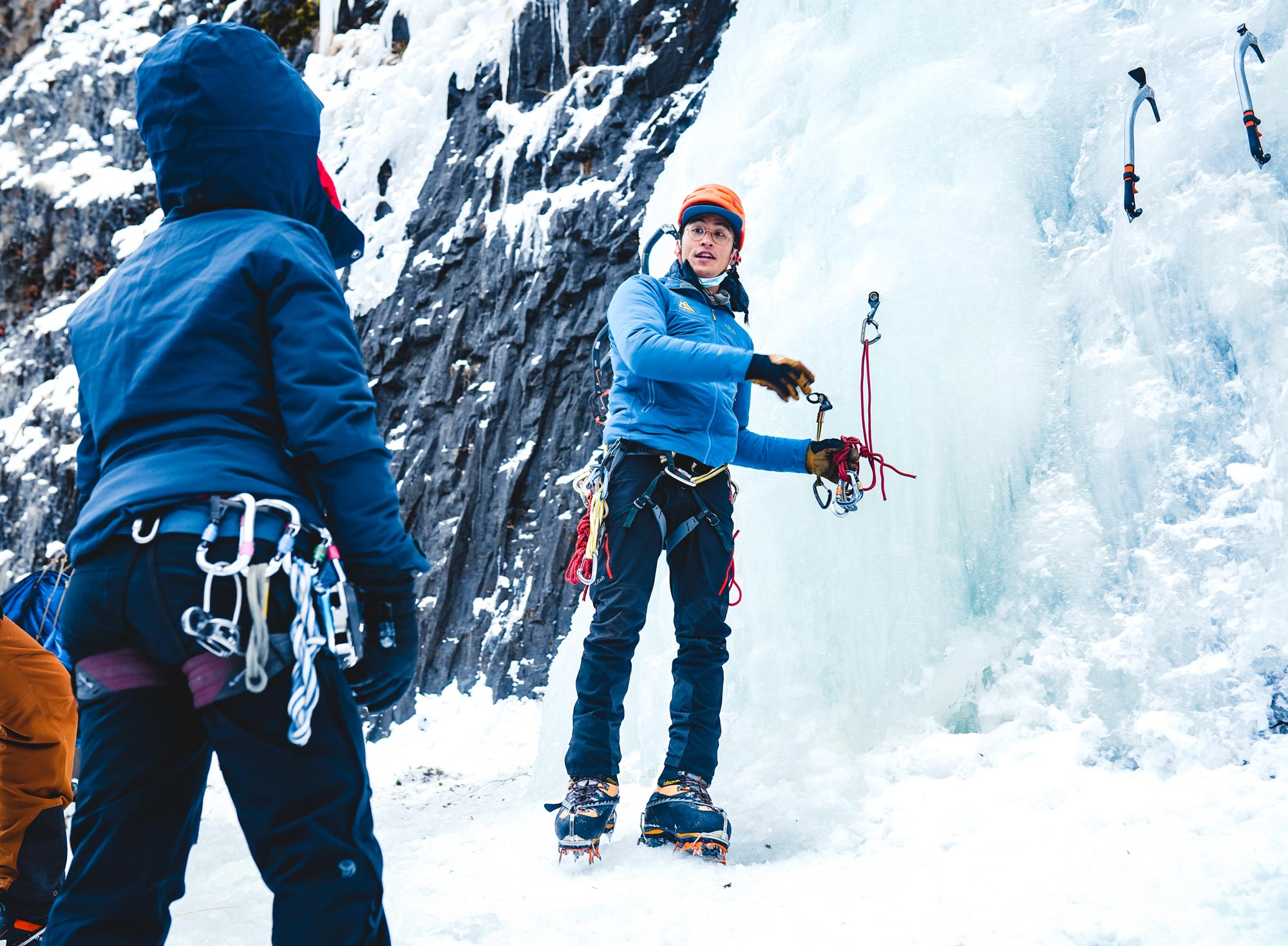 Don Nguyen teaches a BIPOC ice-climbing clinic in Hyalite Canyon, Montana (traditional lands of Apsaalooke, Salish-Kootenai, Northern Cheyenne, Niitsitapi, Confederated Salish and Kootenai and other nations), with Karen de Vera in the foreground.