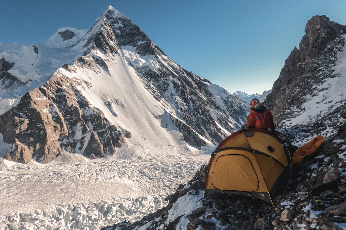 Lunger setting up the tent at the Japanese Camp at 5750 meters. Broad Peak is in the background with the Godwin Austen Glacier below. [Photo] Alex Gavan